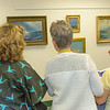 """Staff and patrons of UAF's  Rasmuson Library admire a collection of original paintings by Sydney Lawrence donated to the library from private the collection of alums Tom and Mary Albanese.  <div class=""""ss-paypal-button"""">Filename: DEV-14-4202-5.jpg</div><div class=""""ss-paypal-button-end""""></div>"""