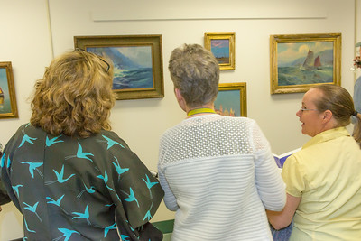 Staff and patrons of UAF's  Rasmuson Library admire a collection of original paintings by Sydney Lawrence donated to the library from private the collection of alums Tom and Mary Albanese.  Filename: DEV-14-4202-5.jpg