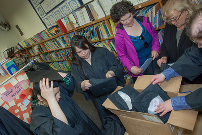 Graduates in the class of 2012 from UAF's Bristol Bay Campus in Dillingham try on their caps and gowns in the comunity library before the commencement ceremony.  Filename: GRA-12-3391-041.jpg