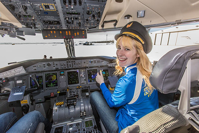 Lilah Hudson, a freshman on the Nanooks' volleyball team, gets a feel for the cockpit inside one of Alaska Airlines' newest aircraft, a Bombardier Q400 turboprop featuring the Alaska Nanooks and UAF.  Filename: DEV-14-4080-42.jpg