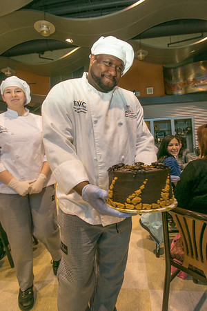 Stephen Beazer models a cake available to the highest bidder during a dessert auction at the 2012 CTC Culinary Arts scholarship banquet.  Filename: DEV-12-3383-202.jpg