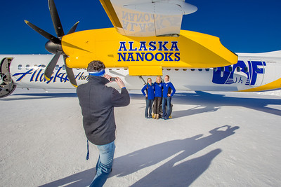 Nanook swimmers pose for a photo under the wing one of the newest planes in the Alaska Airlines fleet, a Bombardier Q400 turboprop, which features the Alaska Nanooks and UAF.  Filename: DEV-14-4080-136.jpg