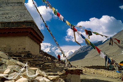 Norbu, the Abbot of Rongbuk Monastery, walks past a large chorten under prayer flags with Mount Everest rising behind.