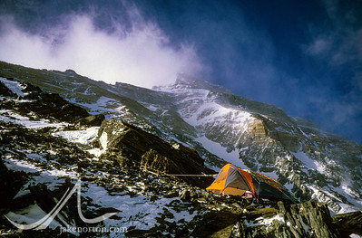 A single tent under a protective cargo net is perched at 25,600 foot Camp V on the North Ridge of Mount Everest, Tibet. The Northeast Ridge and the First, Second, and Third Steps are clearly visible above.