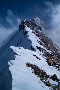 """The crest of the Northeast Ridge of Mount Everest from the top of the Exit Cracks. The First Step is clearly visible in the mid-foreground, with the summit pyramid rising behind. The famed """"Green Boots' Cave"""" is under the obvious boulder to the left and in front of the First Step proper."""