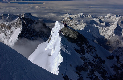 Climbers on Everest's South Summit (28,750 feet) as viewed from the Hillary Step on the Southeast Ridge, Nepal.