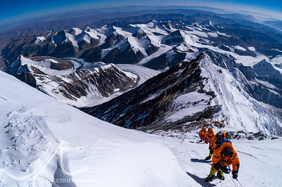 Climbers ascend the Triangle Snowfield of Mount Everest above the Third Step en route to the Dihedrals and on to the summit. The Northeast Ridge stretches out below, with the Kangshung Face on the right of frame.