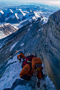A climber approaches the base of the Second Step on the Northeast Ridge of Mount Everest, Tibet, while other climbers below navigate the Corkscrew Chimney.