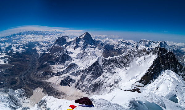 The view from the 29,035 foot summit of Mount Everest at 8:00 AM on May 30, 2003; visible peaks are Lhotse (far right), Makalu, Chomo Lhunzo, and Kanchenjunga (far distant). The Fantasy Ridge - considered Everest's last great problem - is visible in the lower left of the photo, while the upper American Buttress is visible in the center left, below the prayer flags.