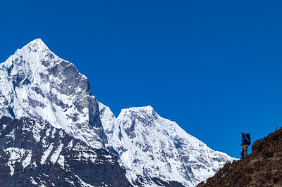 Michael Brown stands beneath the massifs of Tengkangpoche (Tengkangboche) and Bighera-Go Shar while trekking above the village of Khumjung, Solu Khumbu, Nepal.