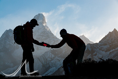 Trekkers silhouetted against the south face of Lhotse with Mount Everest rising behind; in the Khumbu Valley, Nepal.