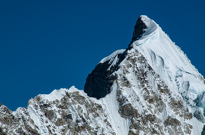 The twirled summit of Khumbutse rises into the vivid blue sky as seen from near Camp 1 in the Western Cwm on Mount Everest, Nepal.