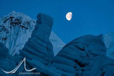 A half moon rises above towering seracs in the Khumbu Icefall, Mount Everest, Nepal.