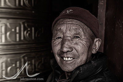 A Tibetan man spins a prayer wheel at Rongbuk Monastery, Tibet.