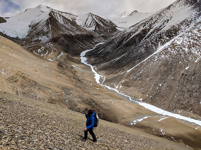 Hiking in the Qianjing Chu valley far above Rongbuk Basecamp on Mount Everest, Tibet, with the north sides of Kellas Rock Peak (AKA Lixin) and Dongfang visible behind.
