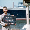 Greg holding sign of Aunt Florence QE cruise - July 12, 1956