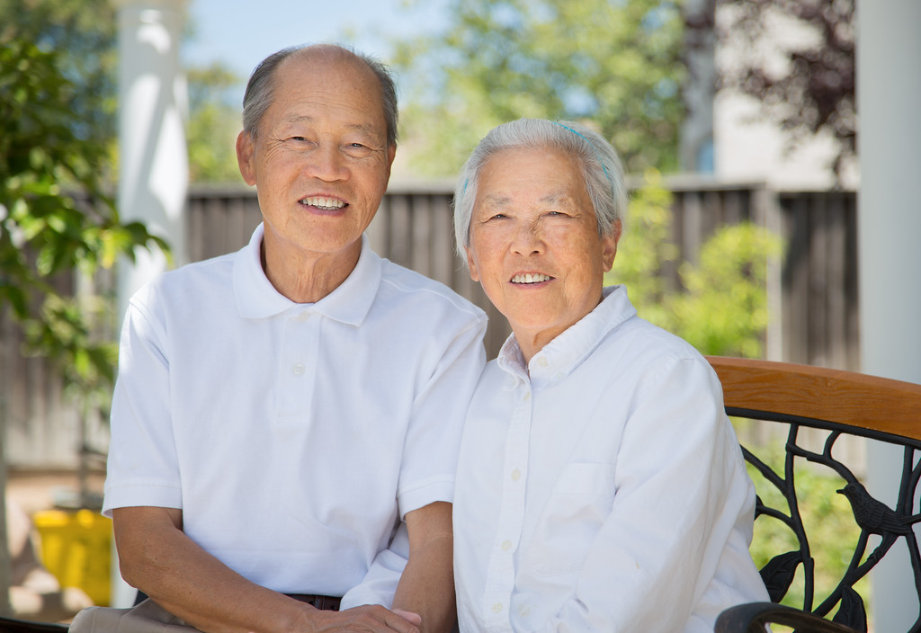 Happy Chinese Elderly Couple Sitting in Back Yard