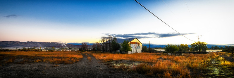 On a brisk, autumn morning, steam rises from the Big Horn River and the sunrise glows on the stock yard barn.