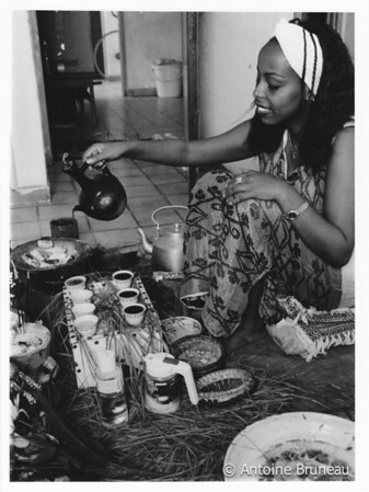 An young Ethiopian woman pouring traditionally brewed coffee from a jebena, a container made from pottery.