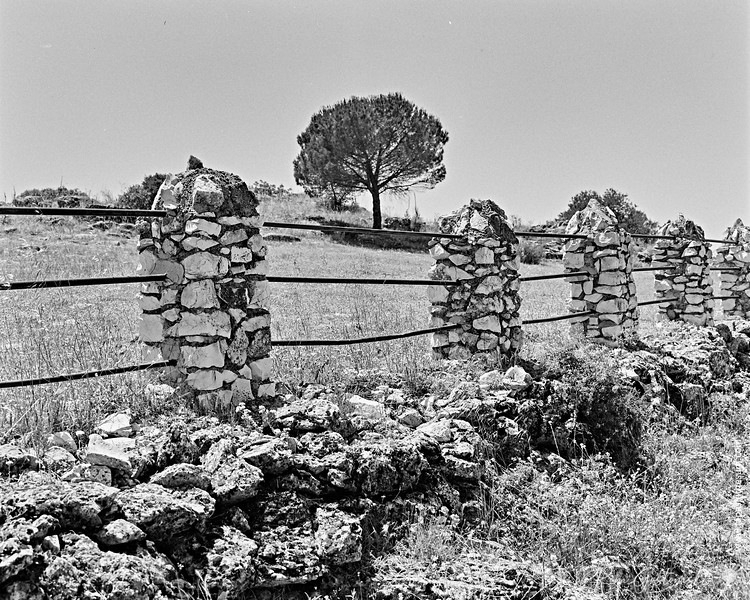Fence with stone posts and metal railings