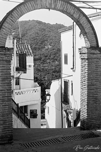 Jubrique - Through the arch. White houses on a steep street
