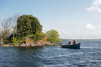 Anglers fishing from a boat on Lough Melvin for Sonaghan and Gillaroo trout passing castle ruins