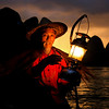 An old fisherman holding the gas lamp on the bamboo raft beside Li river at dusk