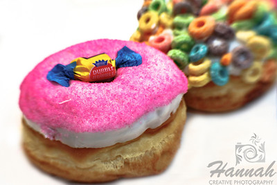 "Fancy doughnuts from Voodoo Doughnut of Portland, Oregon ""Dubble Bubble""... raised yeast doughnut with vanilla frosting, bubble gum dust and a piece of bubble gum  and ""The Loop""... raised yeast doughnut with vanilla frosting and Fruit Loops!  Shot with the Lensbaby composer with sweet 35 optic  © Copyright Hannah Pastrana Prieto"