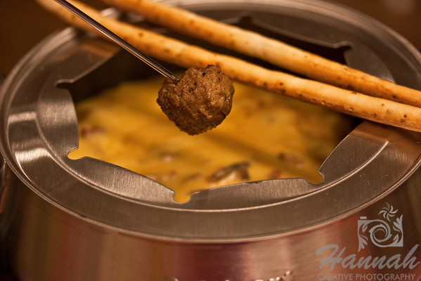 Close-up shot of a meatball being dunked at a cheese bacon fondue with breadsticks on the side in ambient lighting.  © Copyright Hannah Pastrana Prieto