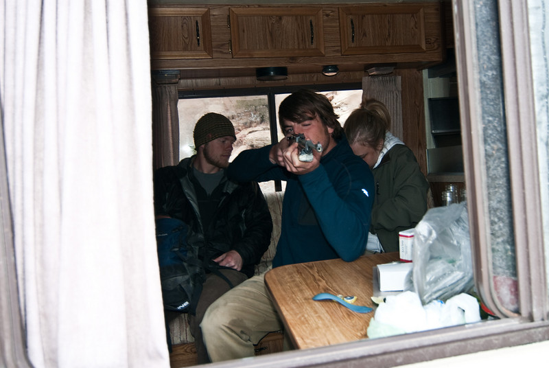 Josh shooting cans out the window of the RV with the BB gun.