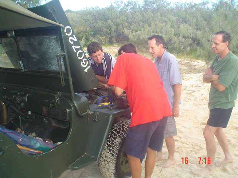 Jeff fixes his starter motor at the beach campsite as Danny, Michael and Emiel look on Photo by J. Gordon