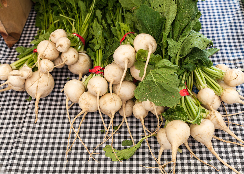 White radishes with greens at a farmer's market
