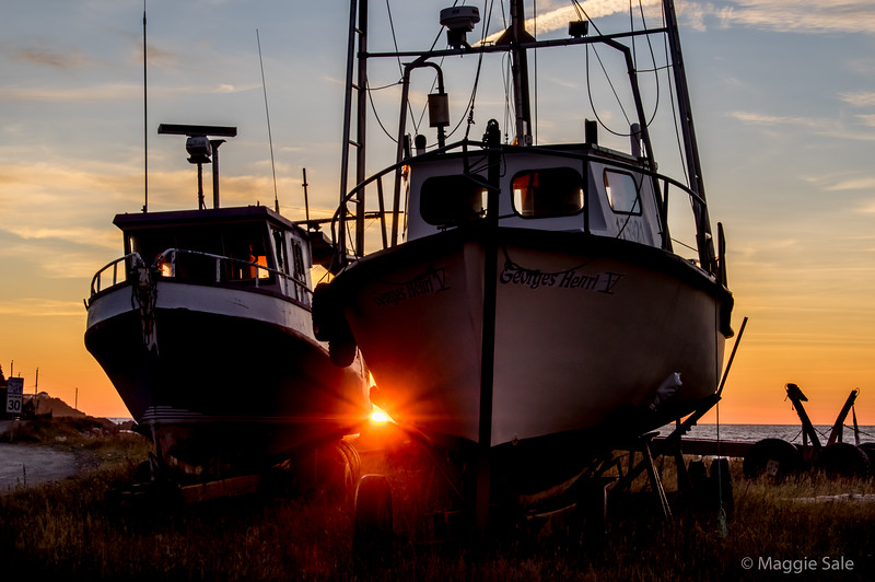 Setting sun between old boats at Tourelle harbour
