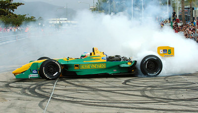 15 JUL 2006 TOWNSVILLE, QLD - Motorsport fans converged on Townsville's Entertainment & Convention Centre for the launch of the Lexmark Indy 300.  Alex Tagliani entertains the crowd with high powered burnouts in his Champ Car - PHOTO: CAMERON LAIRD