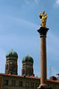 Mariensäule (St. Mary's Column) - erected in 1638, and topped by a gilded statue of the Virgin Mary, to celebrate the end of the Swedish invasion - with the twin brick towers and oxidized copper domes of the Frauenkirche (Church of Our Lady), in the distance - Munich