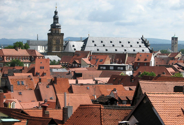 Across the clay tile rooftops - to the St. Martin Church - and the distal tower and spire of the Erlöserkirche (Erloser Church) - with the northern section of the Franconian Alb, mountain range, along the distal horizon - Bamberg