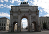 "Sigestor (Victory Gate) - erected in 1852, it is a three-arched triumphal monument to commemorate the bravery of ""the Bavarian army"" (dem bayerischen heere) and its success in the Napoleonic war of liberation - viewing southward down the Luidwig Strasse (street), past the twin-spire towers of the Luidwigkirche (church) on the left, the twin-domed towers of the Theatinerkirche (R), and the Neues Rathaus Turm (New Town Hall Tower) in the distance - Munich"