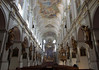 Central nave of the Peterskirche (St. Peter's Church) - with statues and the pulpit upon the piers of the colonnade - frescoes along the nave ceiling - and the high altar at the chancel arch - Munich