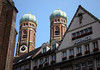 Twin oxidized copper domes and towers of the Frauenkirche (Lady of Our Church) - against the naked Munich sky - Hirmer, a high-end men's clothing company, below.
