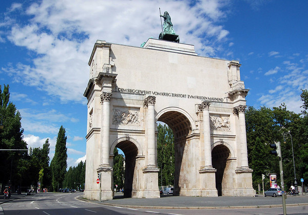 "Sigestor ( Victory Gate) - erected in 1852 - the 3 arched monument stands 69 ft. (21 m) tall, 79 ft. (24 m) wide, and 39 ft. (12 m) deep - the inscription on the back side is reads ""dem sieg geweiht, vom krieg zerstört, zum frieden mahnend"", which translates to ""dedicated to victory, destroyed by war, reminding of peace"" - atop is the statue of Bavaria, standing on a chariot with staff in hand (the lion-guadriga barely visible) - Munich"