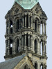 Beyond the gable of the Imperial Cathedral of St. Peter and St. George - to 1 or its 4 Gothic style architectural towers, comprised of depressed arches, columns with socles and capitals, and arcades - and the base of its copper spire (oxidized) - Bamberg