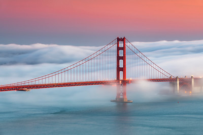 The Golden Gate at dusk with San Francisco blanketed by fog.