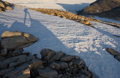 Shadow of backpacker with ice-filled Straits of Denmark in the background.