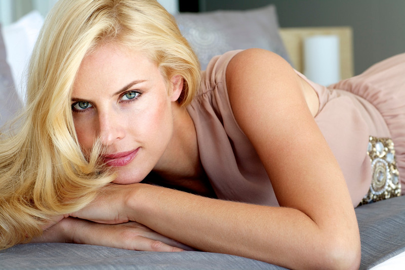Beautiful blonde woman relaxing on a bed