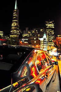 Downtown San Francisco -- March 2008  It was a leisure walk/photoshoot right after yummy italian dinner. Then I just had to stop dead at this wonderful San Francisco skyskape, gorgeous architecture, and .... this lovely reflection from strip clubs' neon sign on this jet black bimmer.   I composed fast like the moment would be gone forever for something that would just sit there the whole night waiting for me to take this picture. I particularly like the main beam from the incoming cars giving it white highlight on the far right of this picture.  Colorful night in San Francisco.