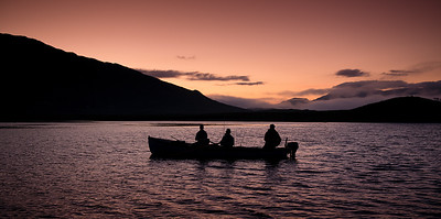 Fishing sunset - fly anglers in a boat Connemara, Ireland fishing for sea trout.