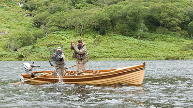 Lough Beagh - Guide nets seatrout for fly fisherman in boat. Glenveagh National Park, Donegal,  Ireland