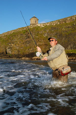 Downhill Co Derry -Flyfisher in sea casting for bass. Mussenden Temple in the background, Downhill, Co. Londonderry, N. Ireland
