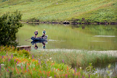 Fin Lough Delphi - Anglers fishing for salmon at Delphi Fishery, Connemara, Ireland. Salmon rises in background.