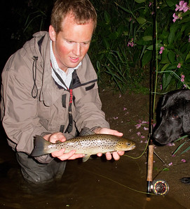 River Slaney - Night fishing for sea trout on River Slaney, Ireland with angler, trout and dog.